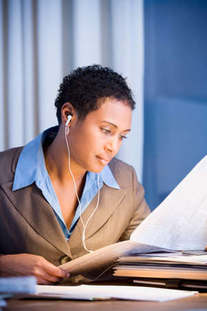 3 persons only: African businesswoman reading newspaper