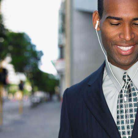 ear buds: African businessman wearing ear buds LANG_EVOIMAGES