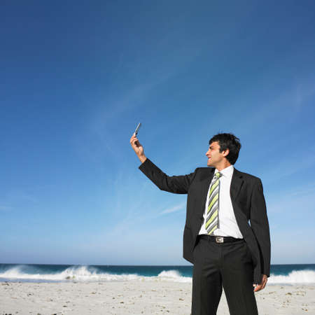 attired: Hispanic businessman looking at cell phone at beach