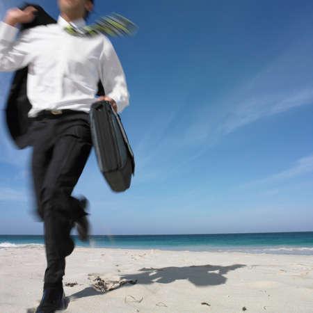 low spirited: Hispanic businessman running on beach LANG_EVOIMAGES