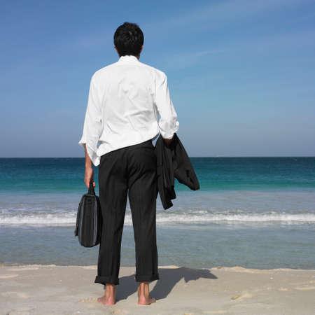 low spirited: Hispanic businessman standing on beach LANG_EVOIMAGES