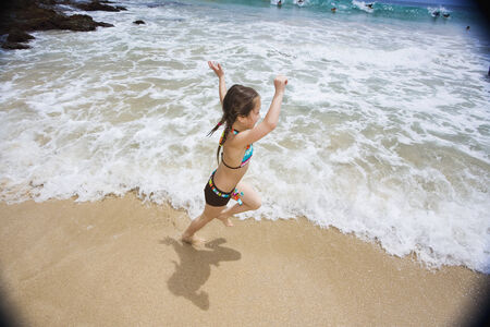 outside shooting: Asian girl running on beach LANG_EVOIMAGES
