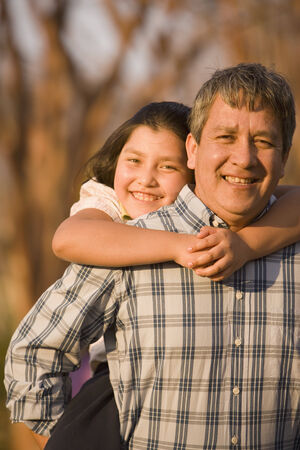 Hispanic father giving daughter piggyback ride