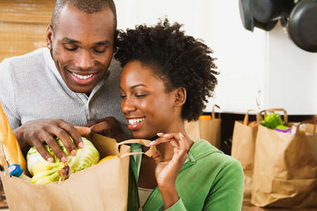 latin american ethnicity: African American couple looking in grocery bag