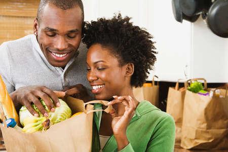 abarrotes: African American joven mirando en bolsa de la compra