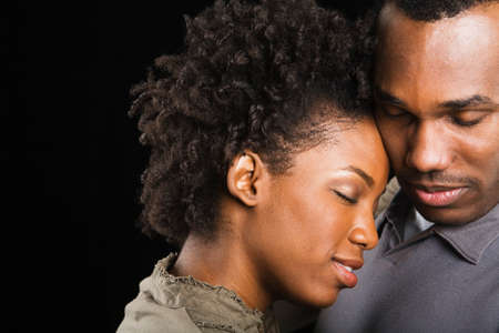 African American couple hugging with eyes closed Stock Photo