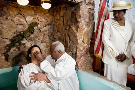 priest's ritual robes: Adult baptism in church LANG_EVOIMAGES