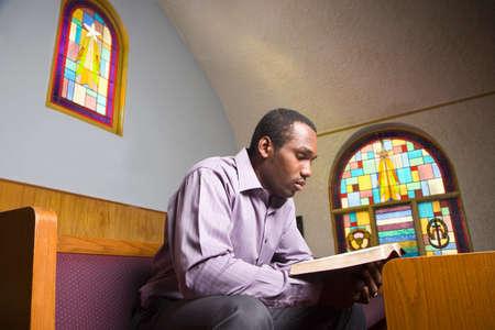 personas saludandose: Hombre afroamericano lectura de la Biblia en la Iglesia