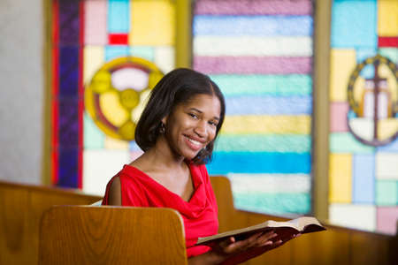 church window: African American woman with Bible in church