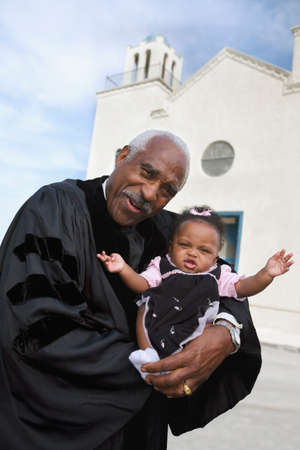 fathering: African American Reverend holding baby