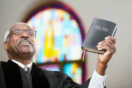 African American Reverend holding up Bible