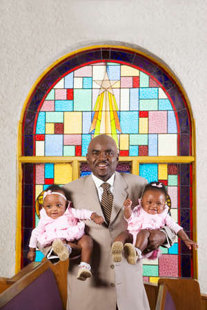 grampa: African American father holding babies in church