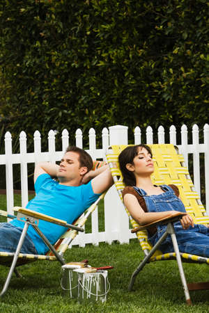 wearying: Multi-ethnic couple relaxing in lawn chairs