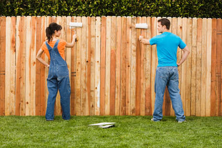 Multi-ethnic couple painting fence