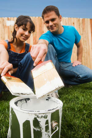 squatter: Multi-ethnic couple holding paintbrushes over can