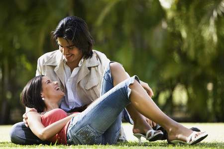 South American couple sitting on grass