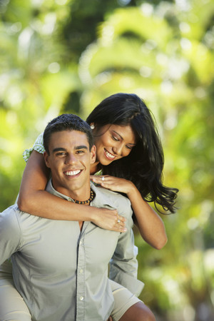 giver: South American man giving girlfriend piggyback ride