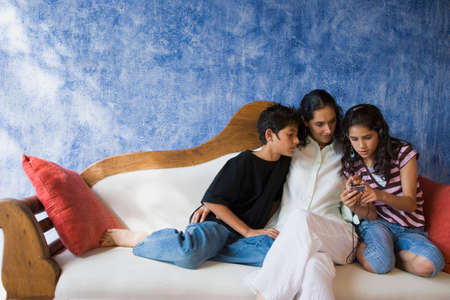 davenport: Hispanic mother and children relaxing on sofa