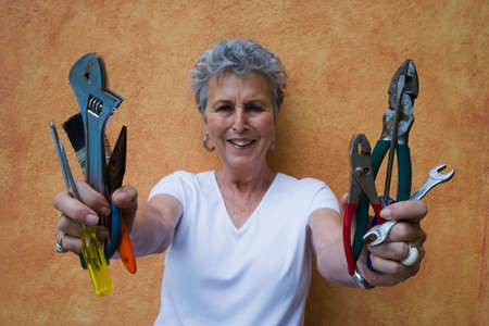 solicitous: Senior woman holding handfuls of tools