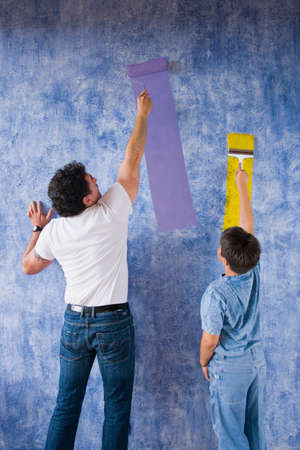 children painting: Hispanic father and son painting wall