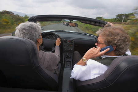 80 plus years: Senior couple driving in convertible car LANG_EVOIMAGES