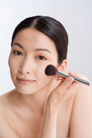 adventuresome: Asian woman applying makeup LANG_EVOIMAGES