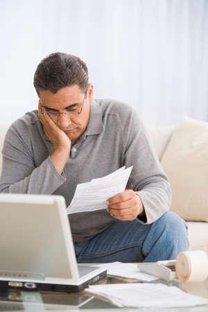 paying: Hispanic man paying bills