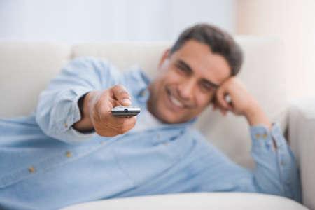 slumbering: Hispanic man pointing remote control