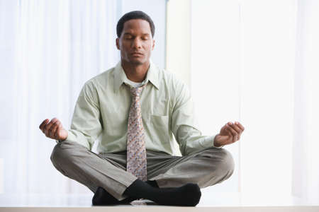 African American businessman meditating on table Stock Photo