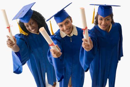 70s tennis: Multi-ethnic female graduates holding diplomas