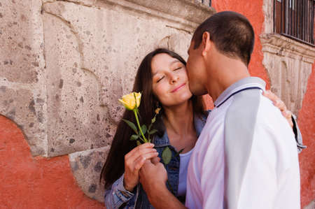america's cup america: Hispanic couple kissing with rose