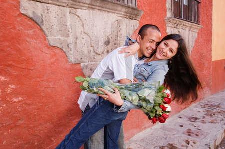 honeymooner: Hispanic couple hugging with roses LANG_EVOIMAGES