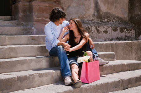 shopping buddies: Hispanic couple talking on cell phone LANG_EVOIMAGES