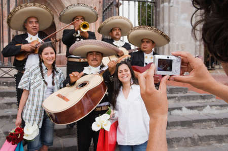 casually: Hispanic women having photograph taken with Mariachi band LANG_EVOIMAGES
