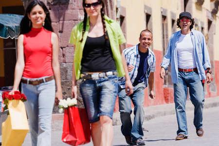 stepping: Hispanic men looking at women in street LANG_EVOIMAGES