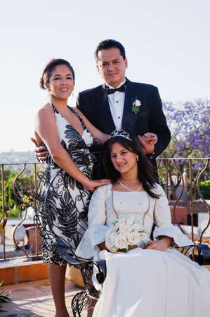 mate married: Hispanic girl with parents at Quinceanera LANG_EVOIMAGES