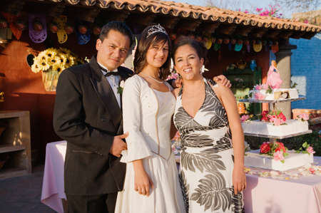 Hispanic girl with parents at Quinceanera LANG_EVOIMAGES