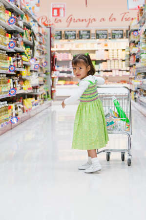finding a mate: Hispanic girl pushing child's shopping cart
