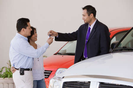 Hispanic couple taking keys from car salesman