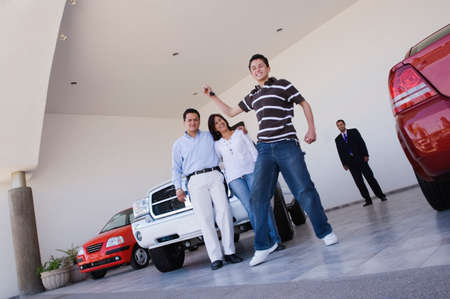 Young Hispanic man holding key for new car LANG_EVOIMAGES