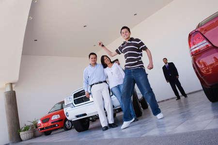 Young Hispanic Mann Holding Schlüssel für neues Auto