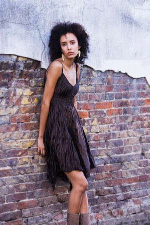 squatter: Mixed Race woman leaning against brick wall