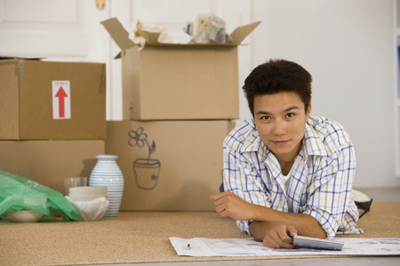 indignant: Asian man next to unpacked moving boxes