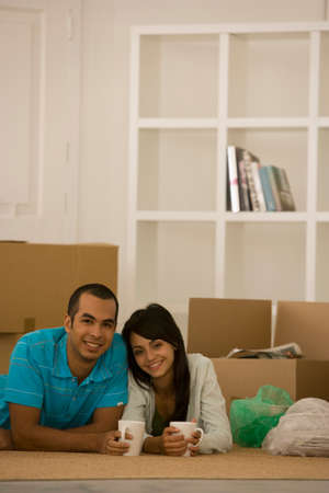unpacked: Young couple next to unpacked moving boxes LANG_EVOIMAGES