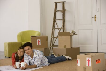 Asian couple on floor next to moving boxes Stock Photo