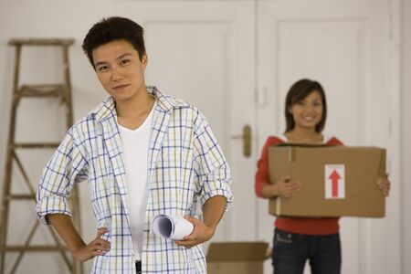 Asian couple with blueprints in new house Imagens