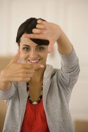 Junge Frau macht Rahmen mit den Fingern