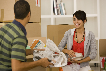 flogging: Young couple packing moving boxes