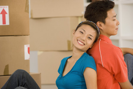 flogging: Asian couple sitting back to back next to moving boxes