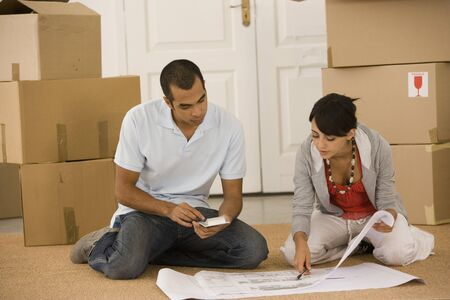 flogging: Young couple looking at blueprints in new house